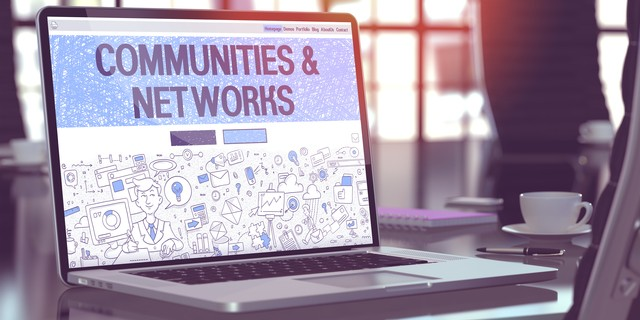 Modern Workplace with Laptop Showing Landing Page in Doodle Design Style with Text Communities and Networks. Toned Image with Selective Focus. 3D Render.