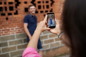 Woman using smartphone to take photo of her boyfriend