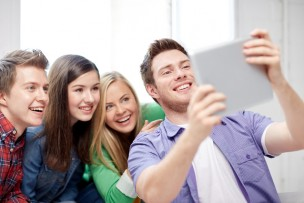 education, people, friendship, technology and learning concept - group of happy high school students or classmates with tablet pc computer taking selfie in classroom