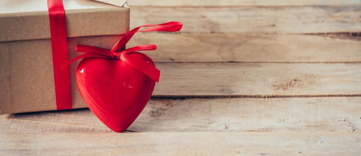 Gift box and red heart on wood table with space
